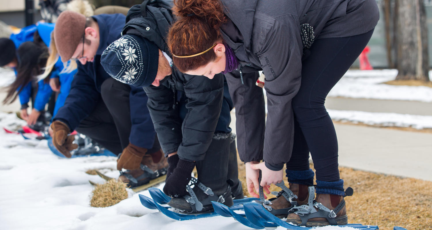 Students strapping on snow shoes